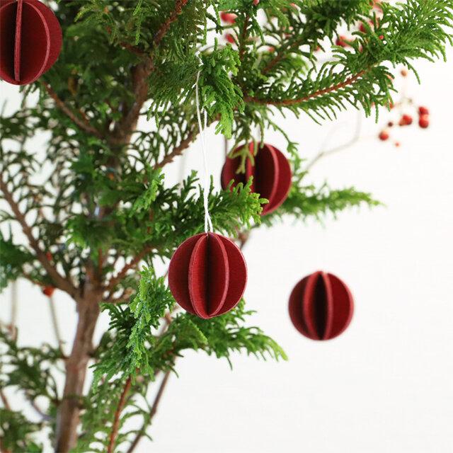 loviのツリー用オーナメント「ボール」は、切り枝に吊るしても◎。木製なので植物にやさしくなじみます(画像は3.5cmダークレッド)。
