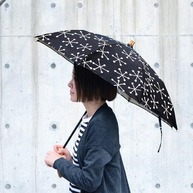 こちらの日傘は、コンパクトに収納できる、二つ折の折りたたみタイプ。持ち手分と石突き部分には、天然の竹を使用しています。たたんだ際には、持ち手の溝にカサの骨がしっかり収納できるなど、細部にまでこだわって作られています。
