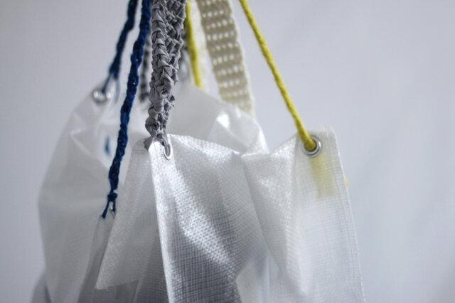 KIT袋にはハトメの金具がついているので、持ち手をつけると便利なバッグになります。 お気に入りの毛糸を三つ編みしたり、細長く編んで持ち手にし、金具に通して留めて簡単につくることができます。 編み物キットだけではなく、KIT袋も自分好みの収納バッグや、エコバッグなどに仕上げてみてください。