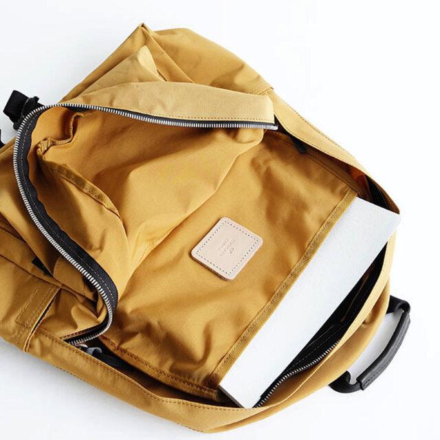 メインのファスナーを開けると書類や雑誌などを分けて収納できる仕切りポケットが付いています。 生地を縫い合わせている箇所は同色のテープでまとめ、ほつれを防ぎ、ヌメ革のブランドネームもついて、バッグの中まで上品な仕上がりを忘れません。