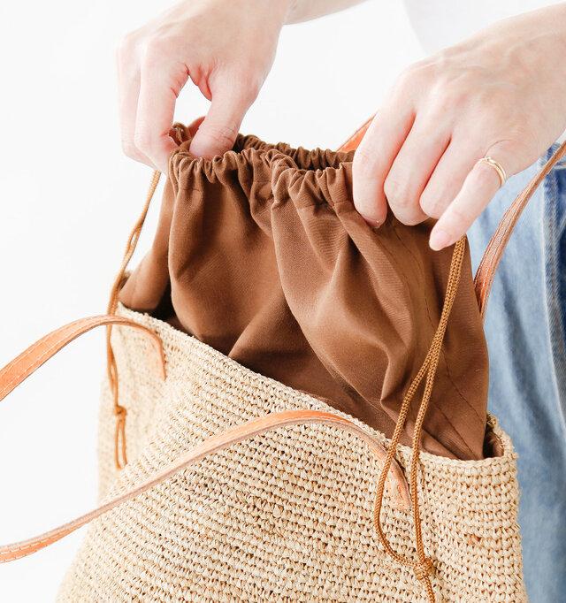 入れ口は巾着式になっており、中身が見えず安心。布は本体と同系色で、スタイリッシュなデザイン。中に織り込んで使用することもできます。