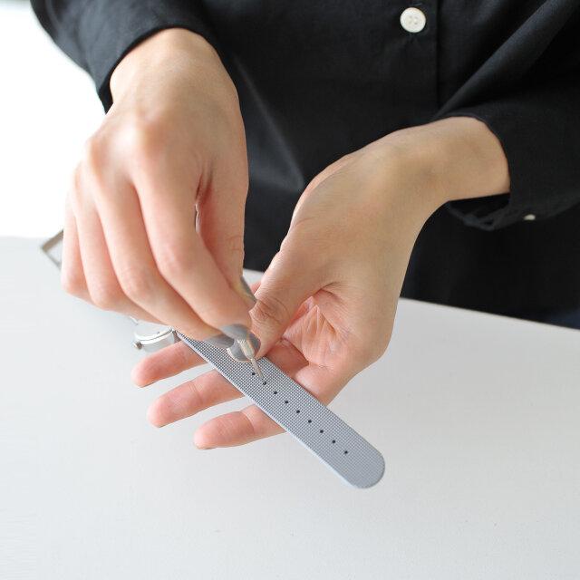Kシリーズの一番の特徴は、そのベルトにあります。裏返すと9つの導き穴が定位置に施されていて、自分の手首のサイズに合わせた穴のみを貫通させるという、特別な体験ができる面白いデザインです。これにより、より自分だけの所有感を感じる時計になっています。