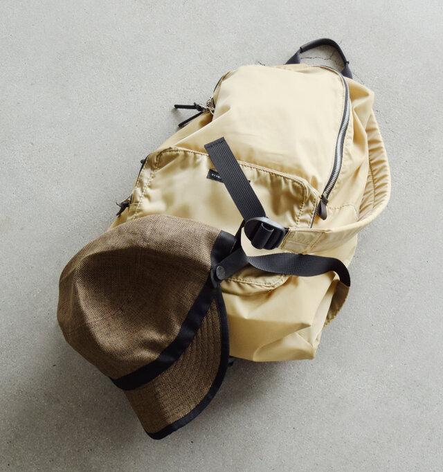 ロゴマークが刻印されたボタンを外してバックパックのショルダー部分や持ち手に留める事が出来ます。バッグに入れる程でもない、ちょっとした時にサッと携帯できて便利です。