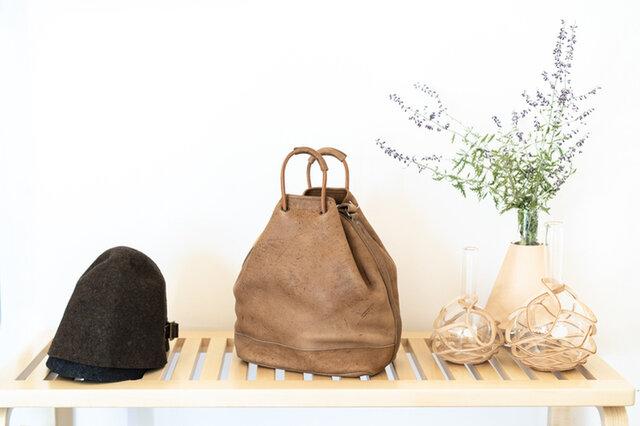 玄関先にArtekベンチを。曲げ木の手法が使われたベーシックでシンプルなデザインは、玄関先でも使い勝手よくマルチに活躍してくれます。物置としてインテリアを楽しむアイテムにもなり、帽子や鞄を置いてお出かけ前の準備にもぴったりです。Hender Schemeの化瓶には庭のお花や植物がたくさん飾れる大き目のサイズを◎ 使い込むごとに艶がでて馴染み丈夫なベジタブルレザーを使用した化瓶と、天然素材を使用し段々と色濃く日焼けしていき経年変化を楽しめるベンチ。どちらも永い間愛着をもってお使い頂けるアイテムです。 ベンチの下には収納ボックスも十分にしまえるので使う用途に合わせて使い方の幅も広がりますね。