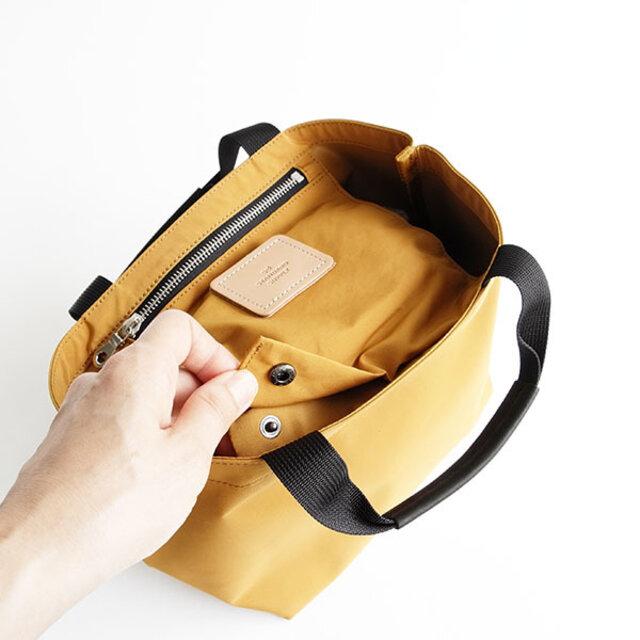 吊りポケットをホックでとめることでフラップになり、中のものを隠すことができます。ハンドルにはグローブレザーを巻いています。