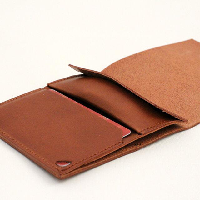 コインポケットの蓋を折り返して縫い付けることで、中央部に膨らみを持たせ多少多めに入る工夫をしておりますが、大量の収納には向いていません。小銭を使わない方でしたらキーポケットとしてもお使いいただけます。  また財布の幅が日本の紙幣より広くなっておりますので、丁度収まるよう札入れガイドの革を内側に付けました。