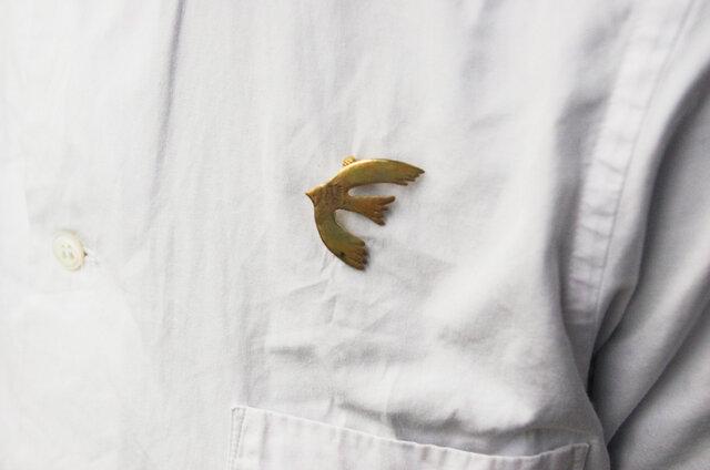 羽根を広げた姿は、どこか愛らしさも。シンプルなシャツのワンポイントに。