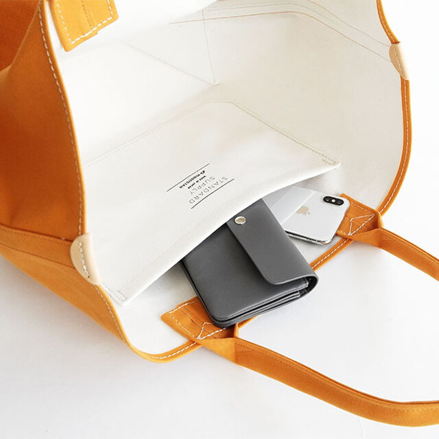 持ち手は生地を二つ折りにしたクッション性の良い丸手ハンドルを採用。 内装には長財布とスマートフォンが入るサイズのポケットがつきます。