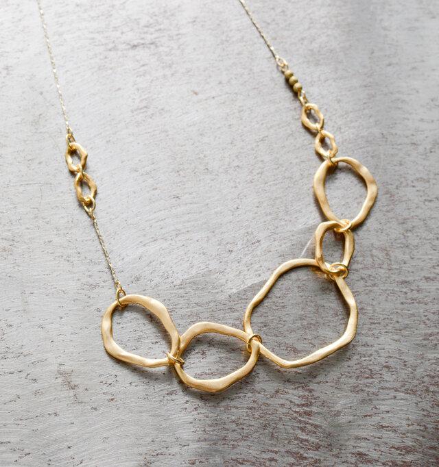 ハンドメイドでつくられたいびつなテクスチャーをもつ大小のリングが連なるデザイン。