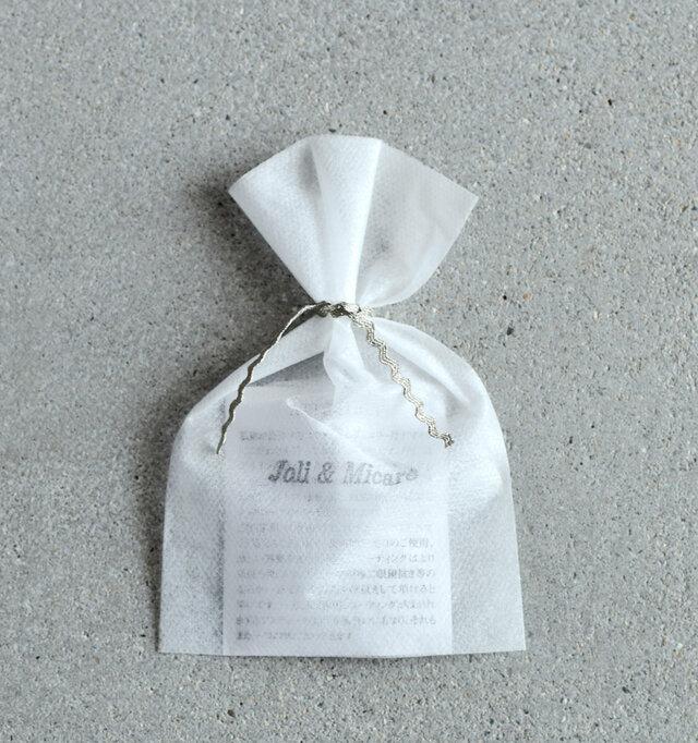 ブランドロゴがプリントされた小さな袋にゴールドリボンをキュッと結んでお届けいたします。