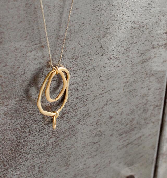 ハンドメイドでつくられた、いびつなテクスチャーが施された大小のリングが連なるデザイン。