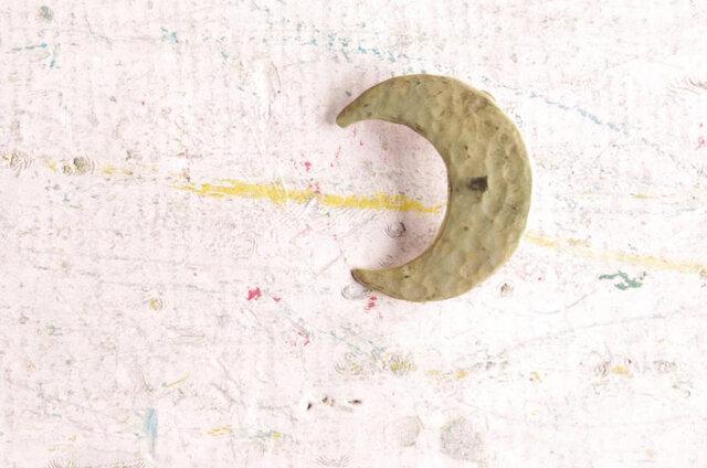 三日月のブローチはそのシンプルゆえ、叩きだしの味わいが存分に楽しめる作品。