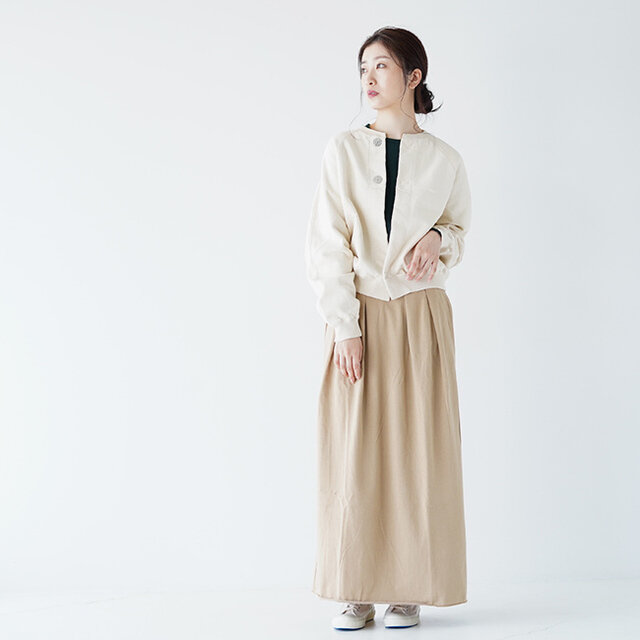 unfil(アンフィル)の白色のカーディガンに、FilMelange(フィルメランジェ)のベージュのスカートを合わせたワントーンコーデ。 ゆったりとしたロングスカートと柔らかい色合いが、ナチュラルで優しい雰囲気を演出。 足元はmoonstar(ムーンスター)のローカットスニーカーで、無駄のないシンプルなデザインが、ワントーンコーデに溶け込み、まとまりのある着こなしに。