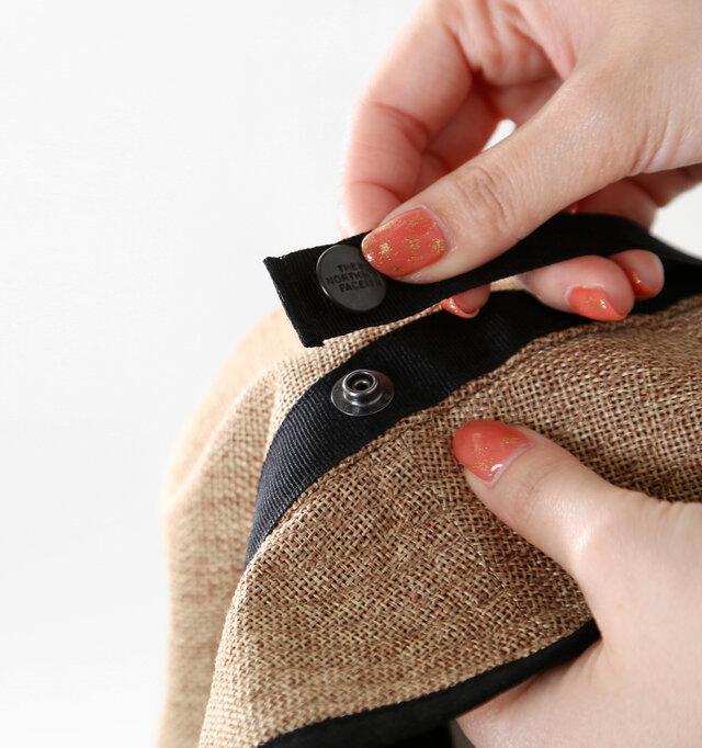 ロゴマークが刻印されたボタンを外してバックパックのショルダー部分や持ち手に留める事が出来ます。