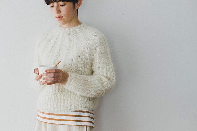 首元から胸元にかけて放射線状に浮き上がる柄と、胴体部分へ続くストンと落ちたシルエットがカジュアルな中にも女性らしい印象のセーター。