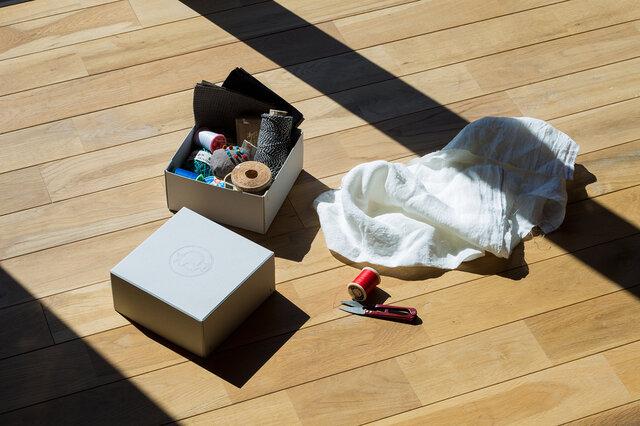 グレーの厚いボード紙をホッチキスで留めたシンプルな正方形の箱は、収納力があり、強度もしっかり。使い捨てでなく、暮らしのなかで使ってほしい一品です。