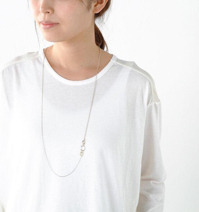 華奢なチェーンと小さなリングの組み合わせが、ノーブルな雰囲気のロングネックレス。 リングモチーフはサイドに配置されたアシンメトリーデザインになっており、さりげなくアクセントを加えます。カジュアルな服に合わせても着こなしを華やかに女性らしく見せてくれる、コーディネートに映えるデザインです。
