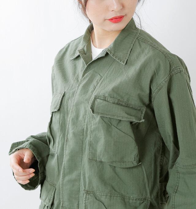 きちんと感のある襟元に、スッキリとした比翼仕立てで、ハードな中に女性らしさも感じられるデザインに仕上げています。きちんと感のある襟と、ひとつだけ表にでた襟もとのボタンがポイントになっています。