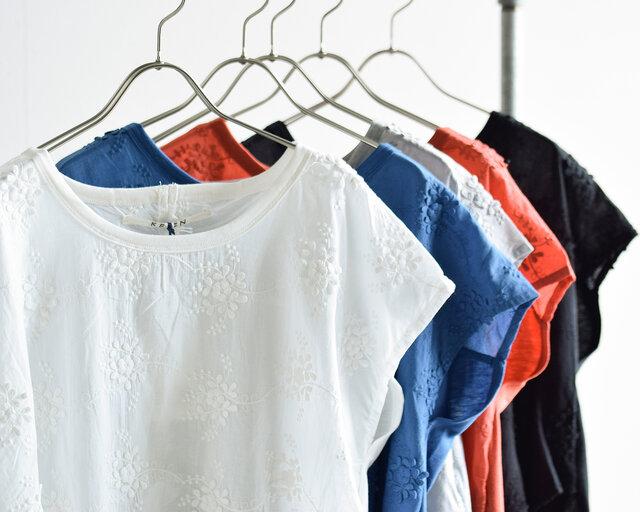 立体的なフラワーレース刺繍が華やかで涼しげな印象のブラウスは、手前からオフホワイト、ブルー、グレイ、オレンジ、ブラックの5カラー展開。どれも夏のおでかけコーデに大人らしさを添える、上品な一枚です。