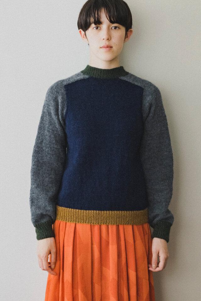 身頃を「ネイビー」、袖と肩部分は「グレー」、襟元と袖口は「グリーン」、裾を「キャメル」に配色を変えて編むデザイン。