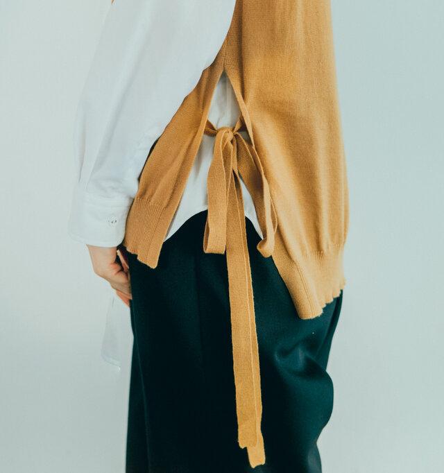 サイドには深いスリットが入っており、ワンピースやロングスカートに重ねても綺麗に着こなせます。 後ろの身頃が少しだけ長くなっています。