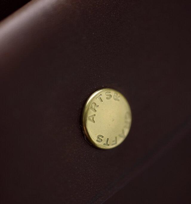 スナップボタンにはブランドロゴが刻印されたオリジナルパーツを使用しています。