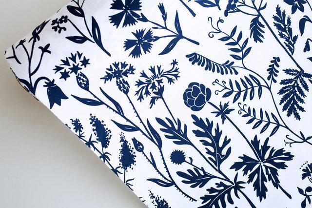 「NIITTYKUKKA」はフィンランド語で「草地の花」という意味の言葉です。その名の通り、様々な種類の草花が白地にネイビーで爽やかに描かれています。花びらや茎、葉の一枚一枚まで繊細に散りばめられたデザインは、ナチュラルでエレガントな雰囲気が漂います。