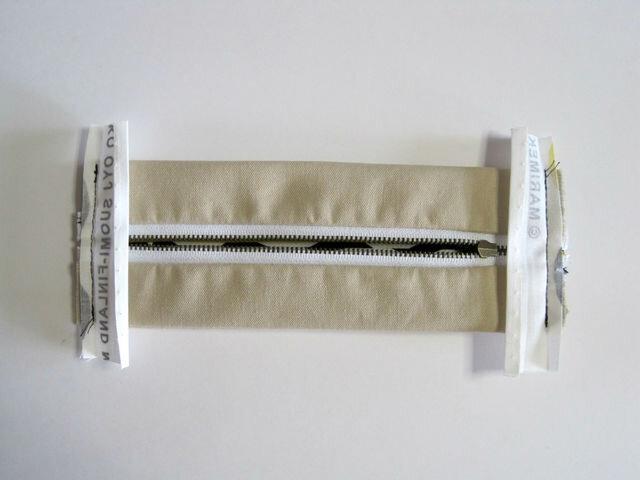 (18)裁断しておいた生地でパイピングテープを2本作り、両サイドをくるむように縫いつけます。