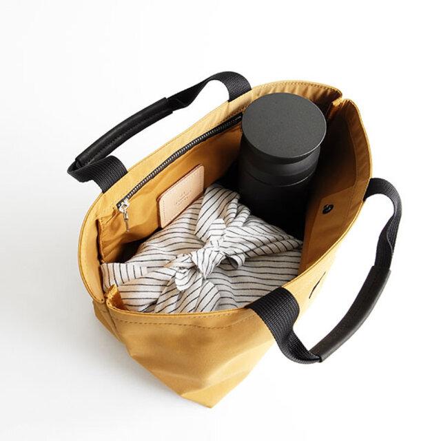 本体生地は64クロスの裏にPVC加工を施したハリのあるものを使用。舟形のトートバッグとして、ものを入れても形が崩れにくく、生地の撚りも少ないため、ステッチもきれいに仕上がっています。