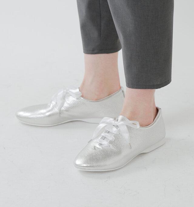 履き口が広めで程よくシェイプされたフォルムのフラットシューズは、サテンリボンを通すことで、より存在感のある一足に仕上がっています。シンプルなスタイリングでも、足もとに素敵なアクセントが加わります。