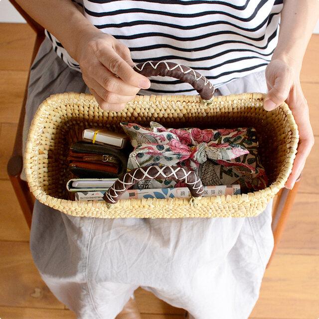 しっかりと手編みされたバッグは、マチもしっかりと付いているので、雑誌やノートはもちろん、お弁当など傾けたくない物を持ち運ぶ際にもおすすめです。手作りのあたたかさ感じる風合いが、なんだか落ち着きますね。  もし、中身が見えてしまうのが気になる方は、お気に入りの布をふわっと被せるのがおすすめです。カゴの中身が見えにくくなるだけでなく、コーディネートのアクセントになりますよ。 (画像はSサイズ)