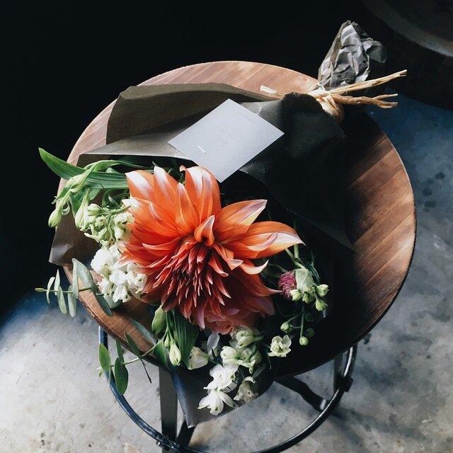 インパクトのあるオレンジ色のダリアを主役に、様々な形の花を組み合わせて、躍動感ある一束に。