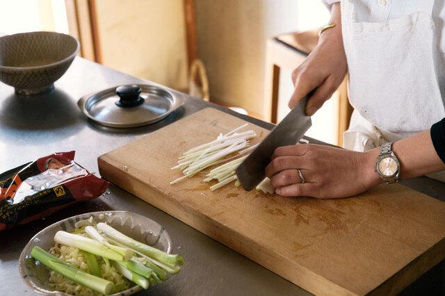 麺を茹でている間にねぎを刻みます。スープは器に入れ熱湯(270cc)で溶かしておきます。