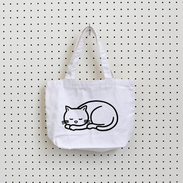 2019年8月、ZUCCaとイラストレーター・Noritakeによるコラボレーション企画「ねむくなる」を機に制作されたアイテム。 目を閉じたネコの描かれた小さめのサイズのトートバッグです。
