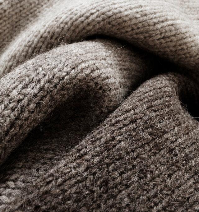 """ペルーのMICHELLE社にて紡績された""""ハイランドウール""""。アンデス山脈の高地ではぐくまれた上質なウールは、保温性がしっかりとあるのにとても軽量。見た目だけではなく実用的なニットです。染色を一切せず、素材そのままの色合いが素朴で温もりのある風合いに仕立てられています。カラーはライトグレー、ブラウングレー、ブラウンの3色をご用意しております。"""