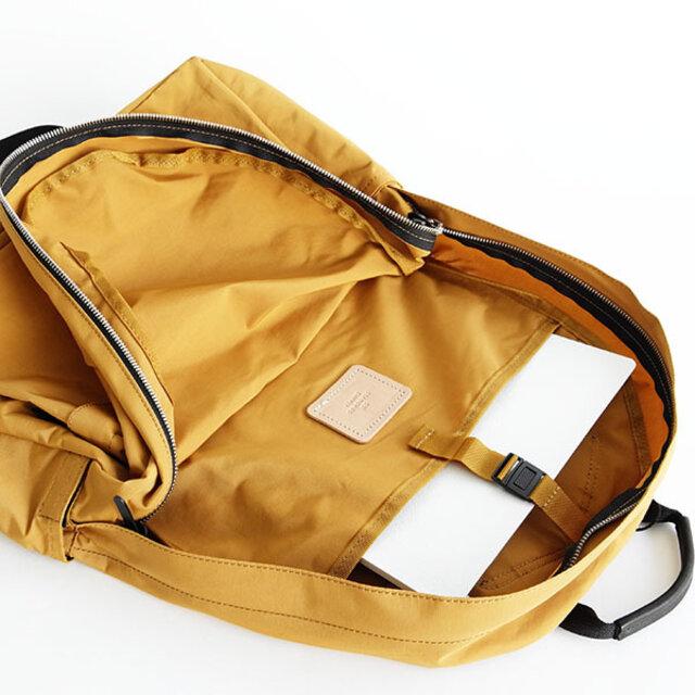 メインのファスナーを開けるとPCや書類、雑誌などを分けて収納できる仕切りポケットが付いています。 生地を縫い合わせている箇所は同色のテープでまとめ、ほつれを防ぎ、ヌメ革のブランドネームもついて、バッグの中まで上品な仕上がりを忘れません。