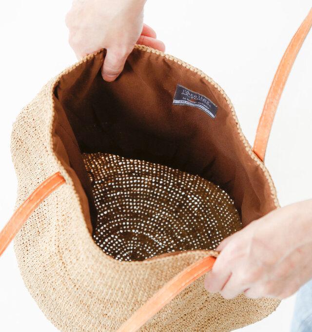 巾着を中に織り込むと、ちょうどロゴタグが内側に見えるようになりますね。底部は円形のマチになっており、深さがあるので日傘やペットボトルなども入り、夏のレジャーや旅行にぴったりなバッグです。