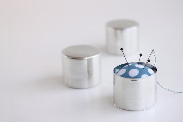 東京下町の職人がひとつひとつ手作りで作る缶に、ドット柄のピンクッションを入れました。 蓋が閉められるので、まち針や糸を付けた縫い針も綺麗に納まり安全です。