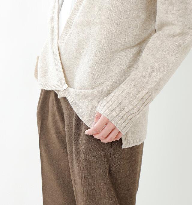裾に小さなボタンをあしらい、女性らしいカシュクールデザインに。程良いドレープ感が上品な雰囲気。