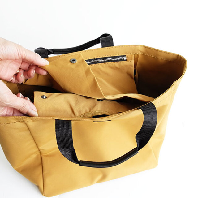 吊りポケットを口元のホックに止めれば、電車内などでも便利なバッグの中を隠せる仕様に。また、フラップをしたままでも取り出せるようなレイアウトにしています。