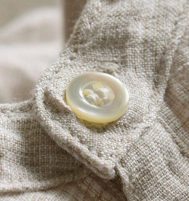 ほんのり透け感と、弾力のあるグレンチェック模様のリネン生地。自然なネップの表情が温かみと深みを感じさせてくれます。縫製後の製品を水洗い(ガーメントウォッシュ)することで素材表面に味がでて、やわらかく素朴な仕上がりになっており、購入後の洗濯における縮みも軽減。ボタンは光の当たる角度によって色を変えながら、美しくきらめきます。