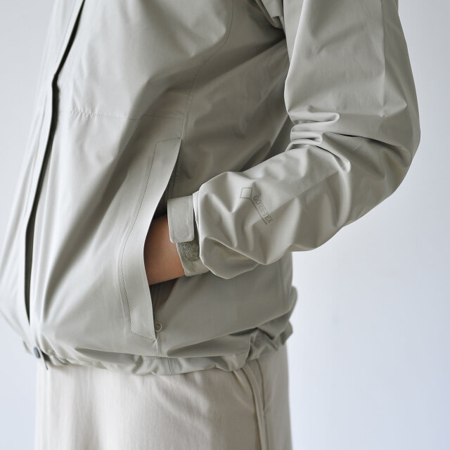 両サイドにフラップ付きのジップポケット。裾にはバタつきを抑えるアジャスターを配置しています。