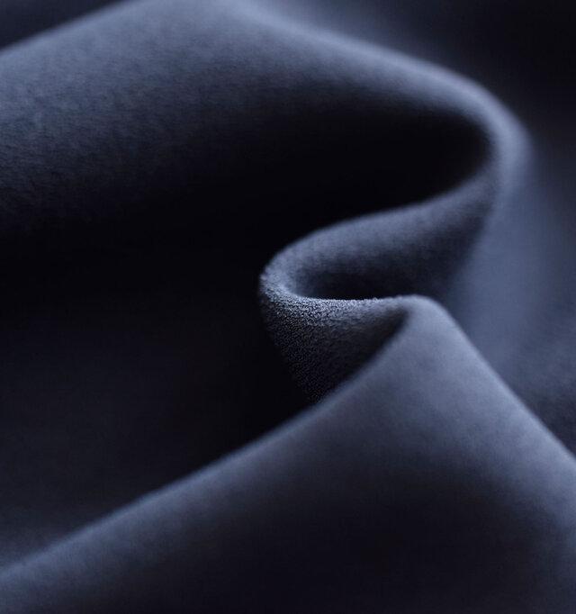acetateとポリエステルの混紡素材を使用し、極細の糸で織り込んだ生地を採用。ややストレッチ性があり、表面にとても細かい凹凸感があるのが特徴で、ざらりとしたニュアンスのある質感です。わずかな光沢感が奥行きのある色合いをつくり出し、高級感漂う生地です。