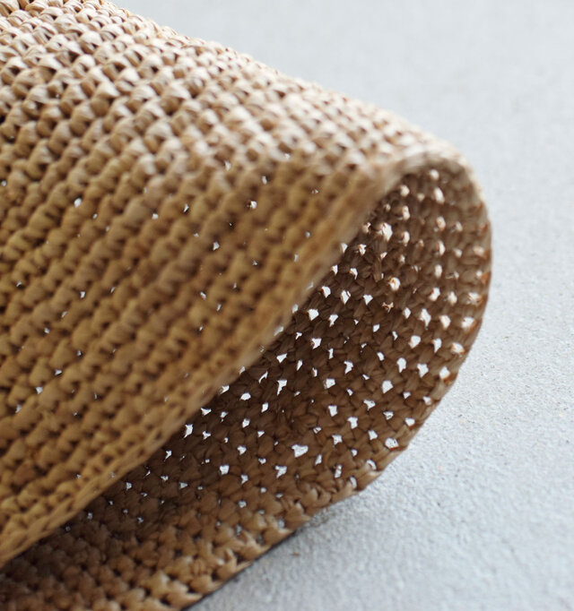 ラフィア椰子の葉の部分を何度も蒸して乾燥させ、内側の柔らかい繊維だけ取り出すという手間のかかる工程を経て作られたラフィア素材は、柔らかくしなやかで、肌触りも優しいのが特徴です。粗密のある編み目で温かな風合いですね。