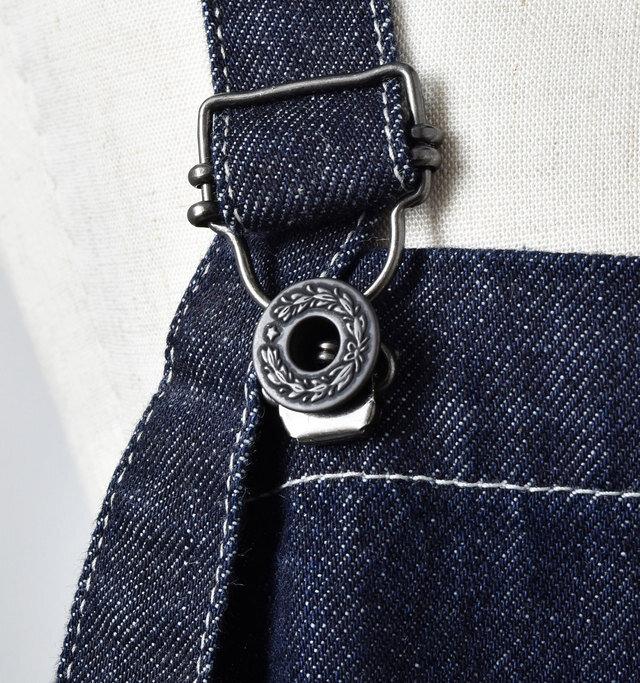 吊りカンで簡単に外せるショルダーは長さ調節も自由自在。模様入りのボタンがいいアクセントになっています。