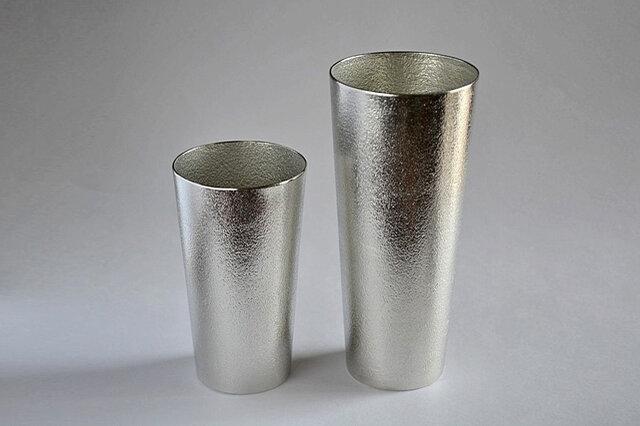 大きさは通常のMサイズ(左)とLサイズ(右)の2種類。Lサイズは350mlのビール缶がちょうど1本入ります。Mサイズは容量約200mlと使い勝手のいい大きさで、特に女性にはおすすめ。裏面には「能作」の印が刻まれています。