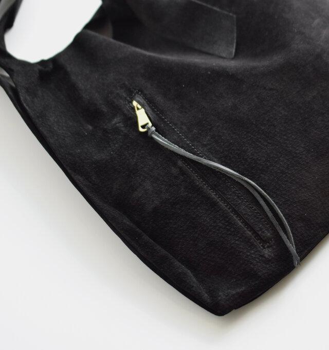 フロントにはポケットを設置。長い革紐付きのチャームで開閉もスムーズです。