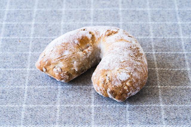 熱心なファンの多いパン。くるみ、ピスタチオ、ひまわりの種、カシューナッツがぎっしり、まさに木の実のパン。小麦と木の実のやさしい旨みが噛むほどにあじわえます。生ハムやチーズ、はちみつなどに合わせて召し上がってください。  原材料 小麦粉、くるみ、ひまわりの種、カシューナッツ、ピスタチオ、塩、パン酵母