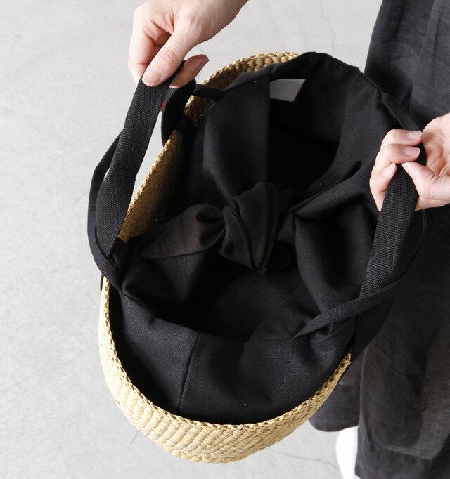大きく中を取り出しやすい入れ口。ボタンなどは付いておらずインナーバッグの上部をキュっと結んで中が見えない仕様になっています。キャンバス地のハンドルは持ちやすく、手にしっくりと馴染んでくれます。