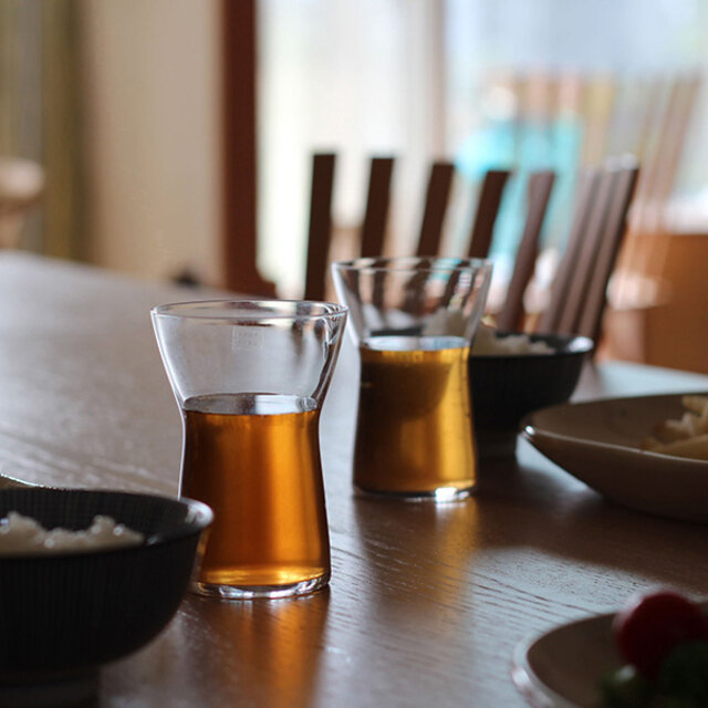 このグラスのデザインは、デンマーク生まれのガラス・陶器デザイナーのTora Urup(トーラ・ウルップ)。 愛知県常滑市の陶器工場でアシスタントとして陶器を学び、その後デンマークとロンドンでも陶器とガラスについて学びました。その後、日本でも有名なデンマークの陶磁器ブランド、ロイヤルコペンハーゲン社を経て、ホルムガード社でデザイナーとして活躍。2001年から自身のデザイン会社を立ち上げ、高い技術を持つヨーロッパや日本の企業とコラボレーションして作品をプロデュースしています。 このグラスは、2006年に日本のガラスメーカー、木村硝子店のコラボレーションして作られました。
